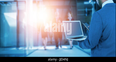 Rear view of businessman using laptop and mobile phone against businesspeople walking in the office - Stock Photo