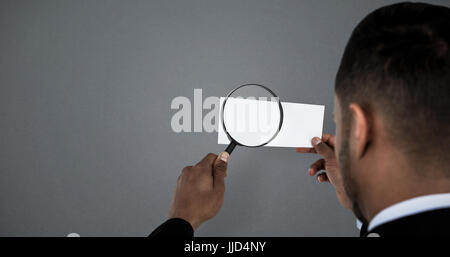 Rear view of man holding magnifying glass on paper against grey background - Stock Photo