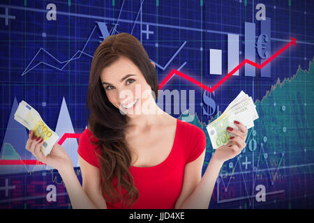 Cheerful brunette holding her cash money  against red arrow - Stock Photo