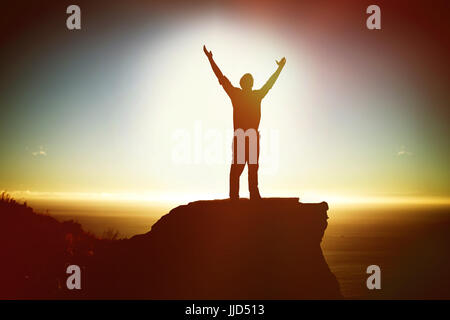 Businessman standing with arms outstretched against scenic view of mountain by sea against sky - Stock Photo