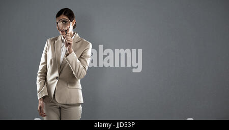 Businesswoman looking through magnifying glass against grey background - Stock Photo