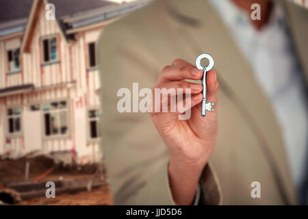 Mid section of business executive showing house key against worker working at construction site - Stock Photo