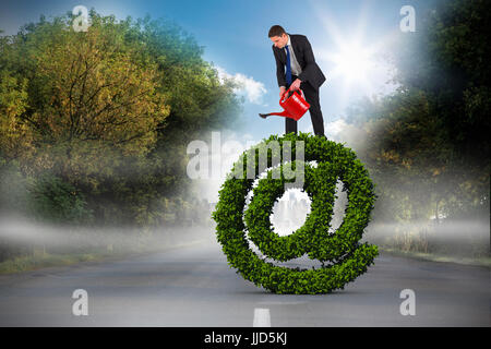 Businessman holding red watering can against open road - Stock Photo