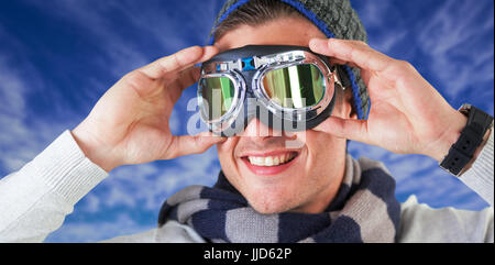Happy man wearing aviator goggles against view of the blue sky
