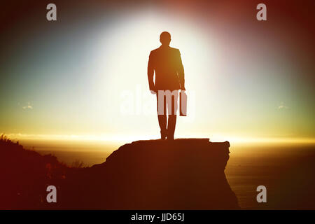 Silhouette man holding briefcase while walking against scenic view of mountain by sea against sky - Stock Photo