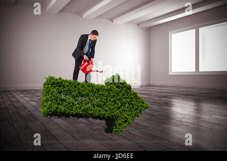 Businessman holding red watering can against white big room with windows - Stock Photo