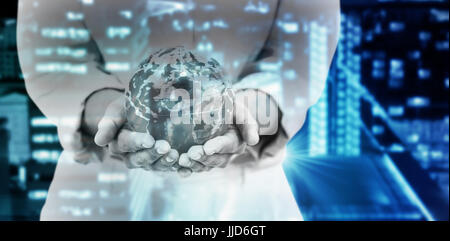 Mid section of businesswoman holding globe against glowing road amidst building in city at night - Stock Photo