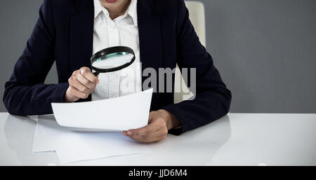Businesswoman looking at document through magnifying glass against grey background - Stock Photo