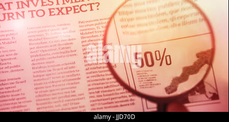flared figure against cropped hand of person holding magnifying glass on graph chart - Stock Photo