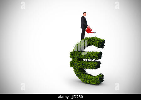 Businessman holding red watering can against euro sign made of leaves - Stock Photo