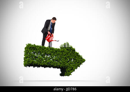Businessman holding red watering can against arrow made of leaves - Stock Photo