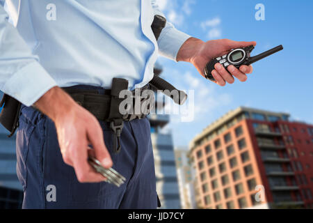 Mid section of security officer holding hand cuff and walkie talkie against modern buildings against sky - Stock Photo