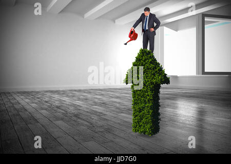 Mature businessman using watering can against white room with windows - Stock Photo