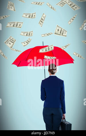 Full length rear view of businesswoman carrying red umbrella and briefcase against blue background - Stock Photo
