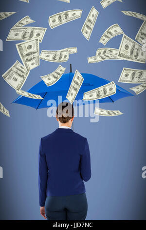 Rear view of businesswoman holding blue umbrella against grey background - Stock Photo