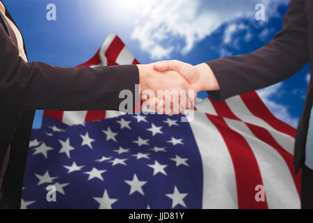 Businessman shaking hands with colleague against blue sky - Stock Photo