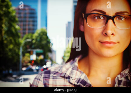 Close up portrait of young woman wearing eyeglasses  against blur view of a modern city - Stock Photo