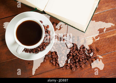 Silhouette of the world against cup of coffee with coffee beans and book - Stock Photo