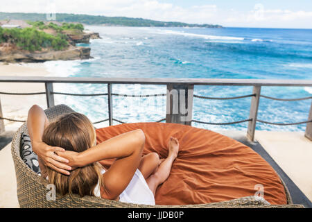 Young happy woman relaxing in lounge on roof veranda with beautiful tropical sea view. Positive girl look at ocean - Stock Photo