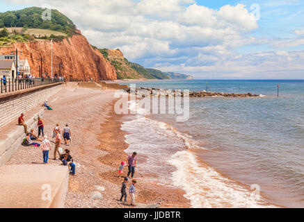 3 July 2017: Sidmouth, Dorset, England, UK - Visitors on the shingle beach on a bright summer day. - Stock Photo
