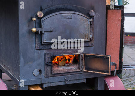 Interior fireplace in a corner with firewood and ax in an old country house - Stock Photo