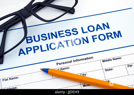 Business Loan Application Form with ballpoint pen and glasses. - Stock Photo