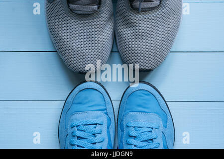 two pairs of sport sneakers toe to toe. man's grey and women's blue smaller. fitness for two. on blue background. - Stock Photo