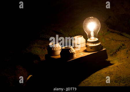 one lightbulb out of four other. A metaphor of the right decision. - Stock Photo