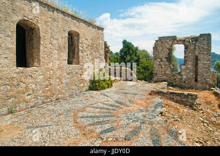 ruins of small 12th century byzantine church with pebble mosaic of sun on floor with mountains and sea at background, - Stock Photo
