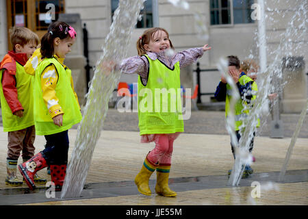 A little girl playing in a water fountain at Barnsley PALS Garden, South Yorkshire, UK. - Stock Photo