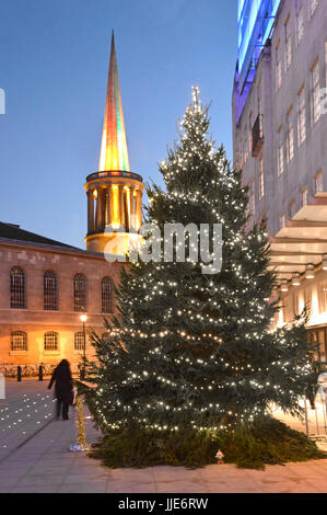 BBC broadcasting house Christmas tree & lights in the new large courtyard with floodlit spire of All Souls Church - Stock Photo