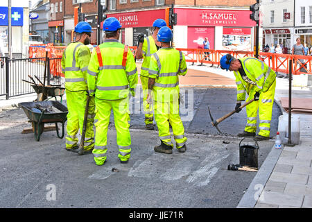 Group of workmen resurfacing town centre road one man using pick axe four others taking short break all wearing - Stock Photo