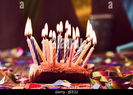 a small cake topped with some lit candles before blowing out the cake, on a rustic wooden table, sprinkled with - Stock Photo