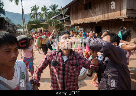 A man is offered a shot of lao-lao (rice whisky) at a wedding procession in Muang Hat Hin, Laos. - Stock Photo