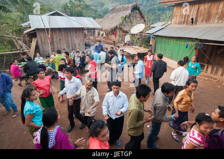 Robert Hahn, Mung, and other partygoers dance in traditional Lao style during a wedding celebration in Muang Hat - Stock Photo
