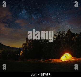 A camping tent under milky way sky and twilight at night - Stock Photo