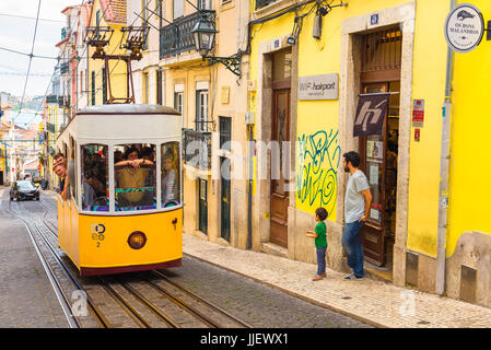 Lisbon tram street, a father and son watch a tram carrying tourists ascend the Elevador da Bica in the Bairro Alto - Stock Photo