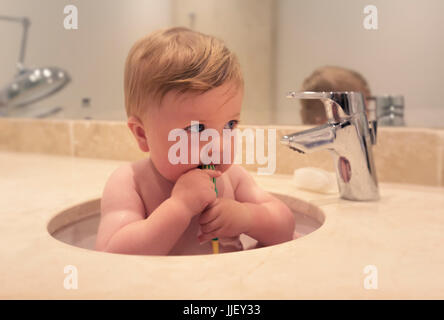 Baby boy sitting in a sink brushing his teeth - Stock Photo