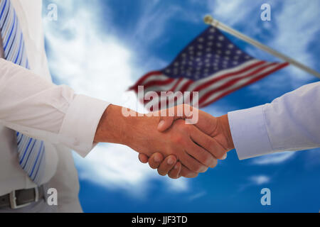 Close-up shot of a handshake in office against blue sky with clouds - Stock Photo
