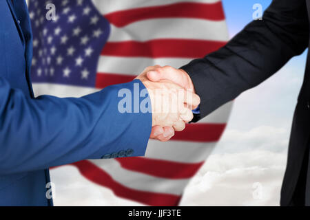 Male executives shaking hands against blue sky with white clouds - Stock Photo