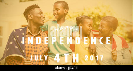 Computer graphic image of happy 4th of july text against happy family with american flag on sunny day - Stock Photo