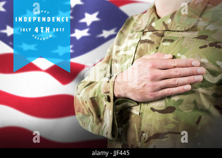 Mid section of soldier in uniform taking oath against focus on usa flag - Stock Photo