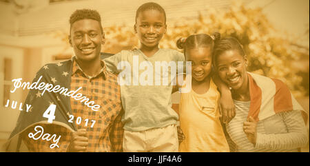 Digitally generated image of happy 4th of july message against portrait of family with american flag on sunny day - Stock Photo