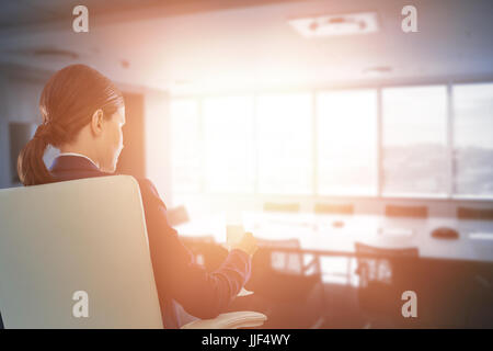 Rear view of businesswoman holding water glass while sitting on chair against empty boardroom in office - Stock Photo