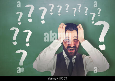 Portrait of frustrated businessman against green chalkboard - Stock Photo