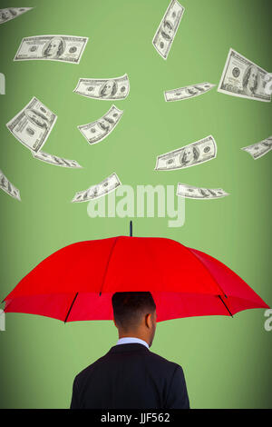 Rear view of businessman carrying red umbrella  against green background - Stock Photo