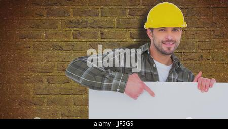 Digital composite of Male architect holding billboard while standing against brick wall - Stock Photo