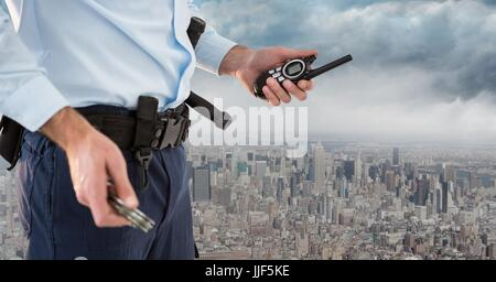 Digital composite of Security guard lower body with walkie talkie against skyline and clouds - Stock Photo