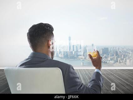 Digital composite of Rear view of businessman sitting on chair holding glass of alcohol while looking at city - Stock Photo