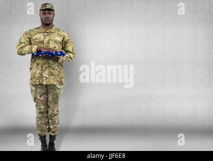 Digital composite of soldier with USA flag in the hands. Concrete room - Stock Photo